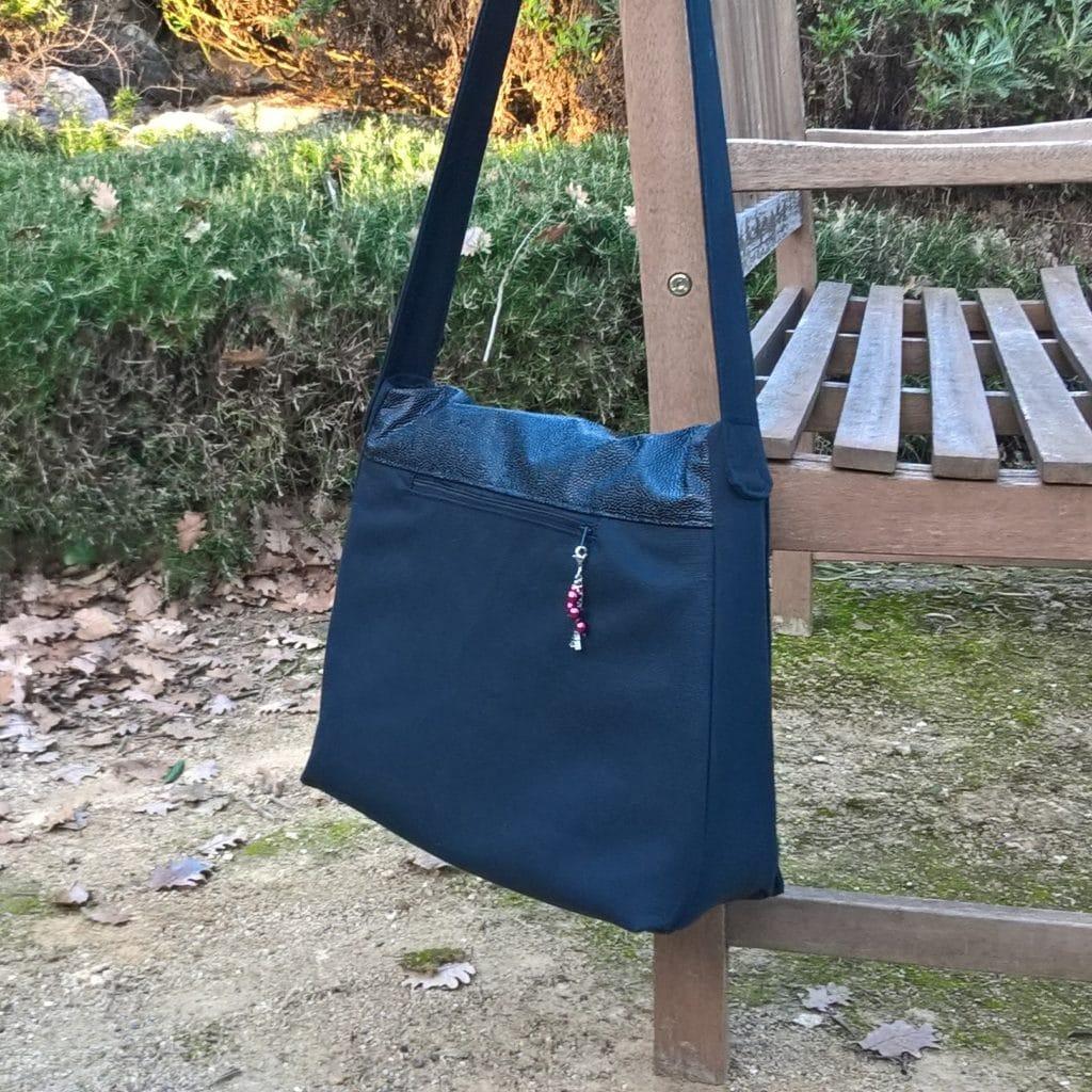 Grand sac cabas suspendu sur le dossier d'un banc de jardin
