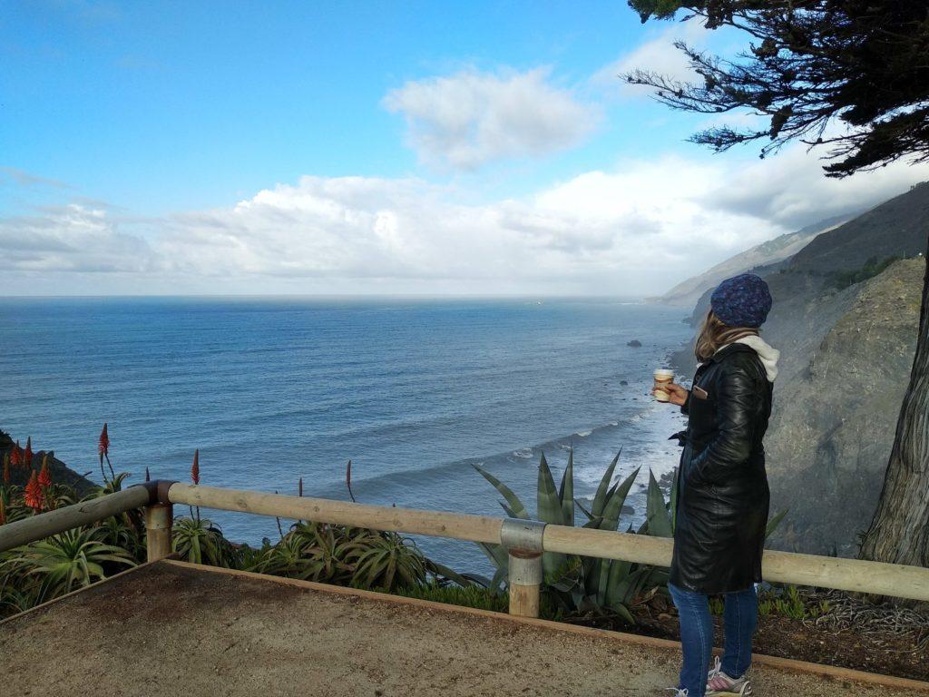 Femme avec un bonnet et une doudoune, qui regarde au loin