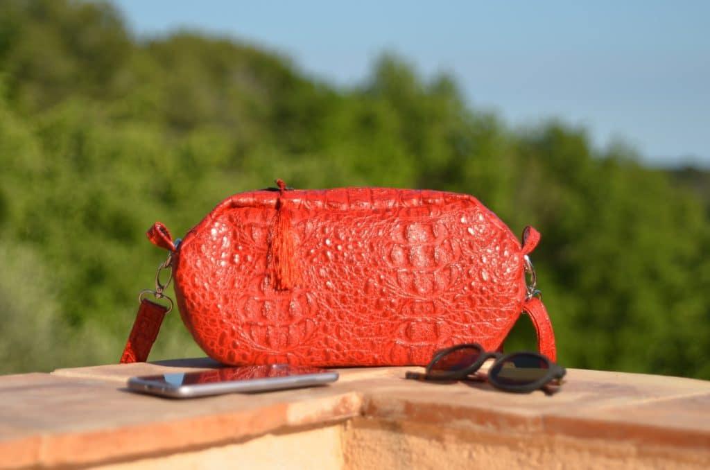Pochette bandoulière rouge coquelicot posée sur un mur ave un téléphone et des lunettes de soleil