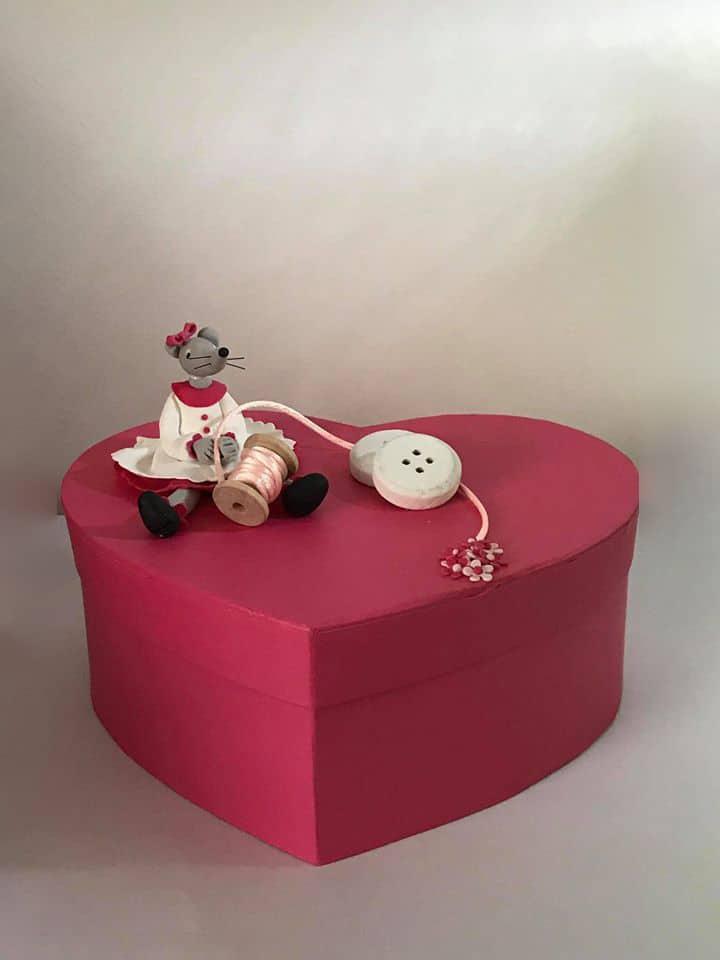 Boite rouge en forme, sur laquelle est assise une petite souris, modeler en porcelaine froide