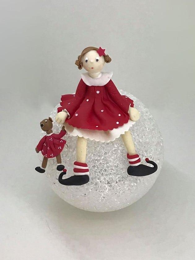 Petite fille en rouge avec son doudou, assise sur une lampe boule, modeler en porcelaine froide