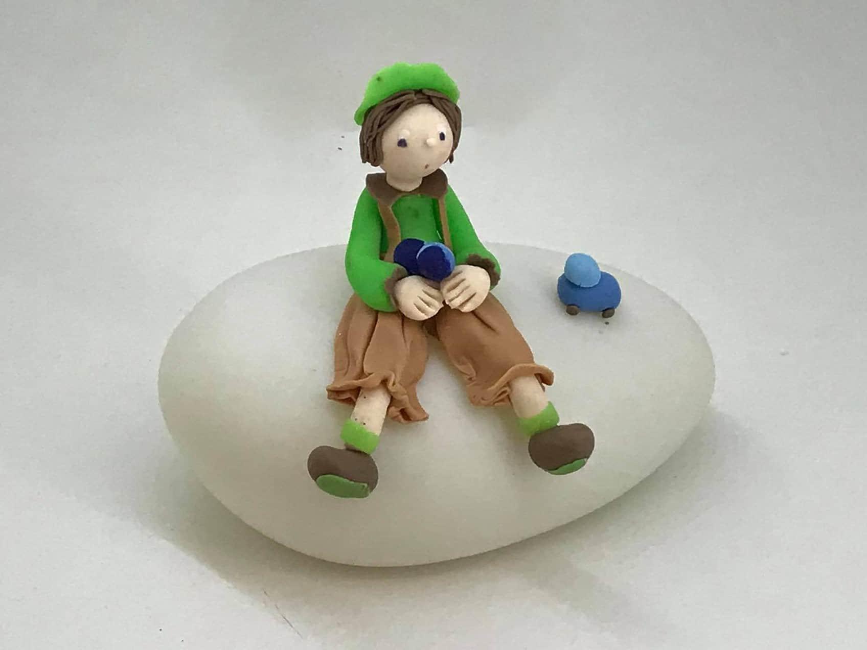 Garçon assis sur une lampe boule, modeler en porcelaine froide