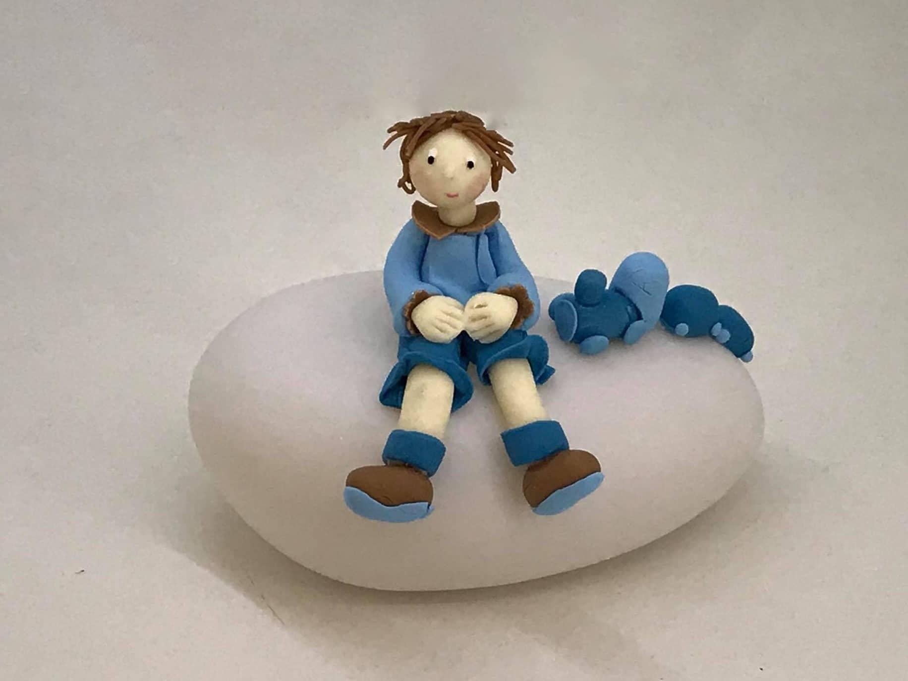 Figurine petit garçon en bleu, sur une boule lumineuse