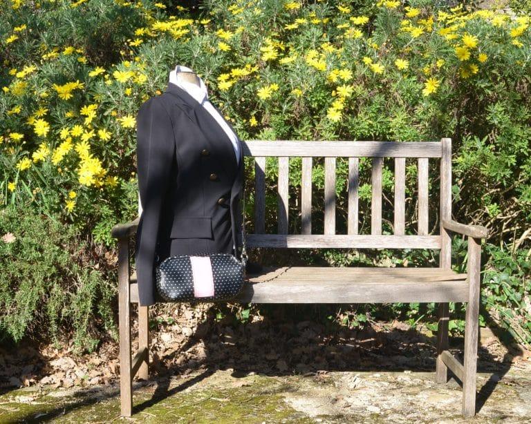 Mannequin posé sur un banc, avec une veste noire et les sac à pois argentés sur fond noir, porté en bandoulière.