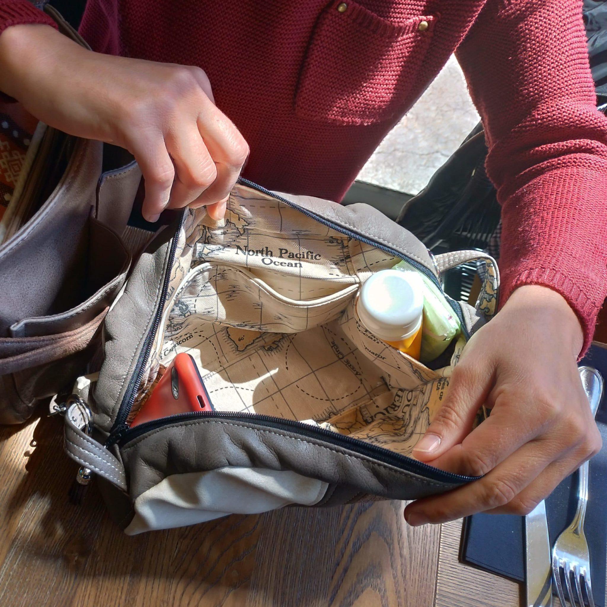 Intérieur du petit sac avec un téléphone et une crème solaire