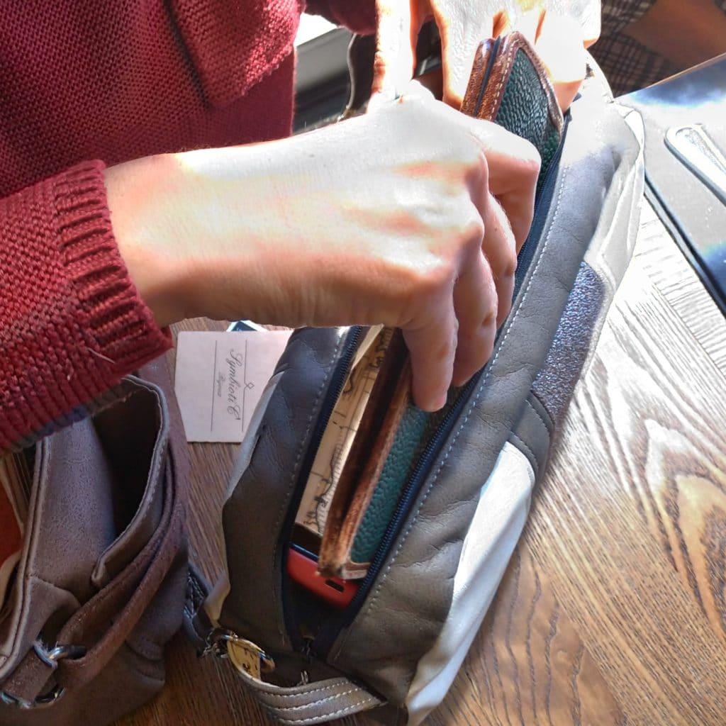 Femme qui met son portefeuille dans son petit sac