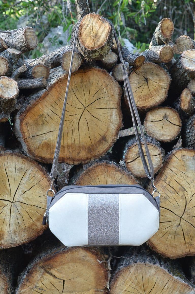 Petit sac en bandoulière blanc et gris avec une fermeture éclaire sur le dessus, suspendu à une bûche dépassant du tas de bûches.