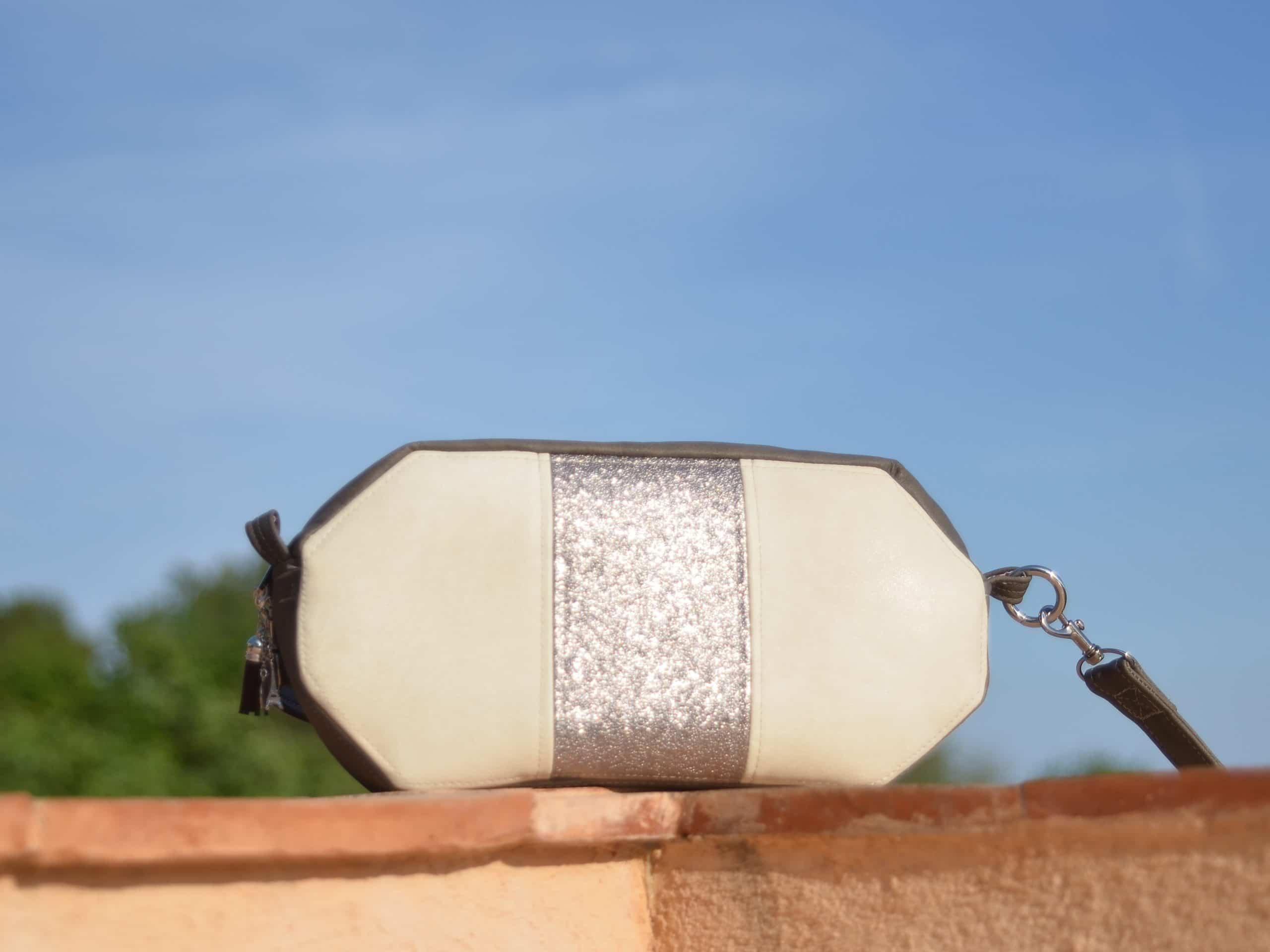 Sac de forme octogonale, blanc et taupe, posé sur le rebord du mur