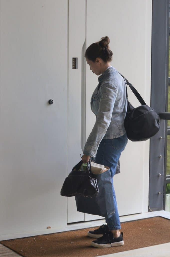 Femme qui vient de fermer sa porte d'entrée et qui part de chez elle surchargée de sacs