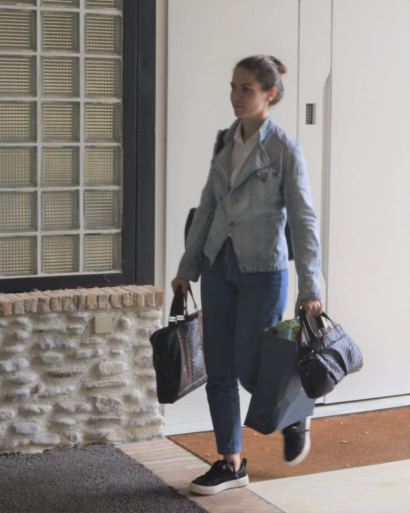 Femme surchargée de sacs qui part de chez elle