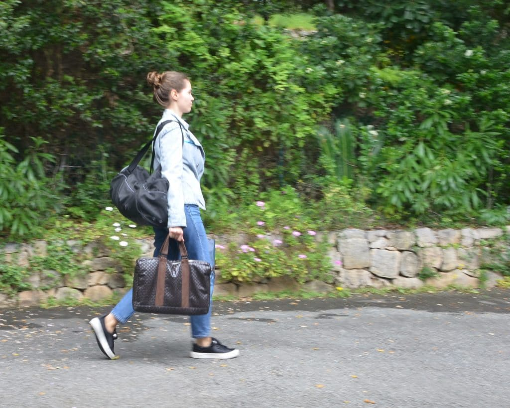 emme portant son cartable, son sac de sport, un sac poubelle, son sac à main qui marche activement sur un chemin