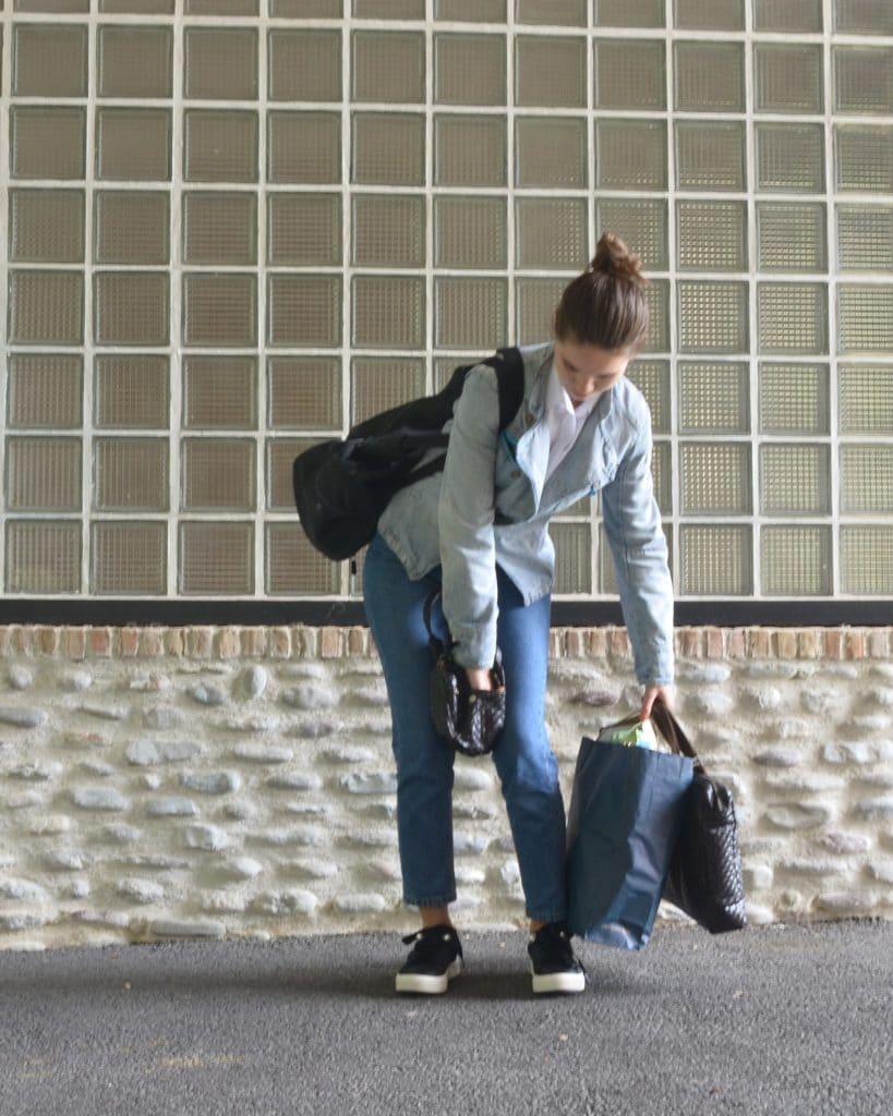 Femme qui a calé son sac à main entre les jambes pour pouvoir y chercher quelque chose