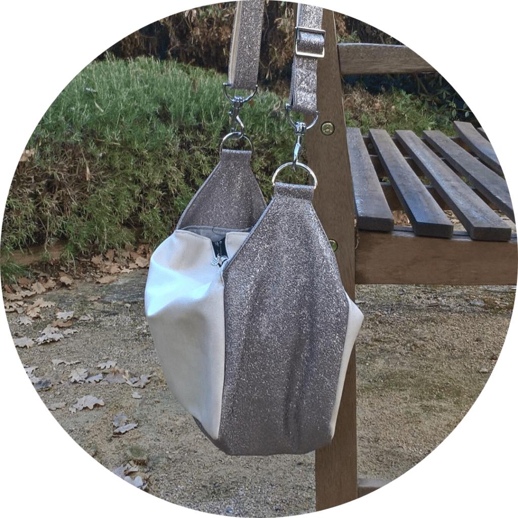 Sac bandoulière de forme cubique suspendu au dossier d'un banc de jardin.