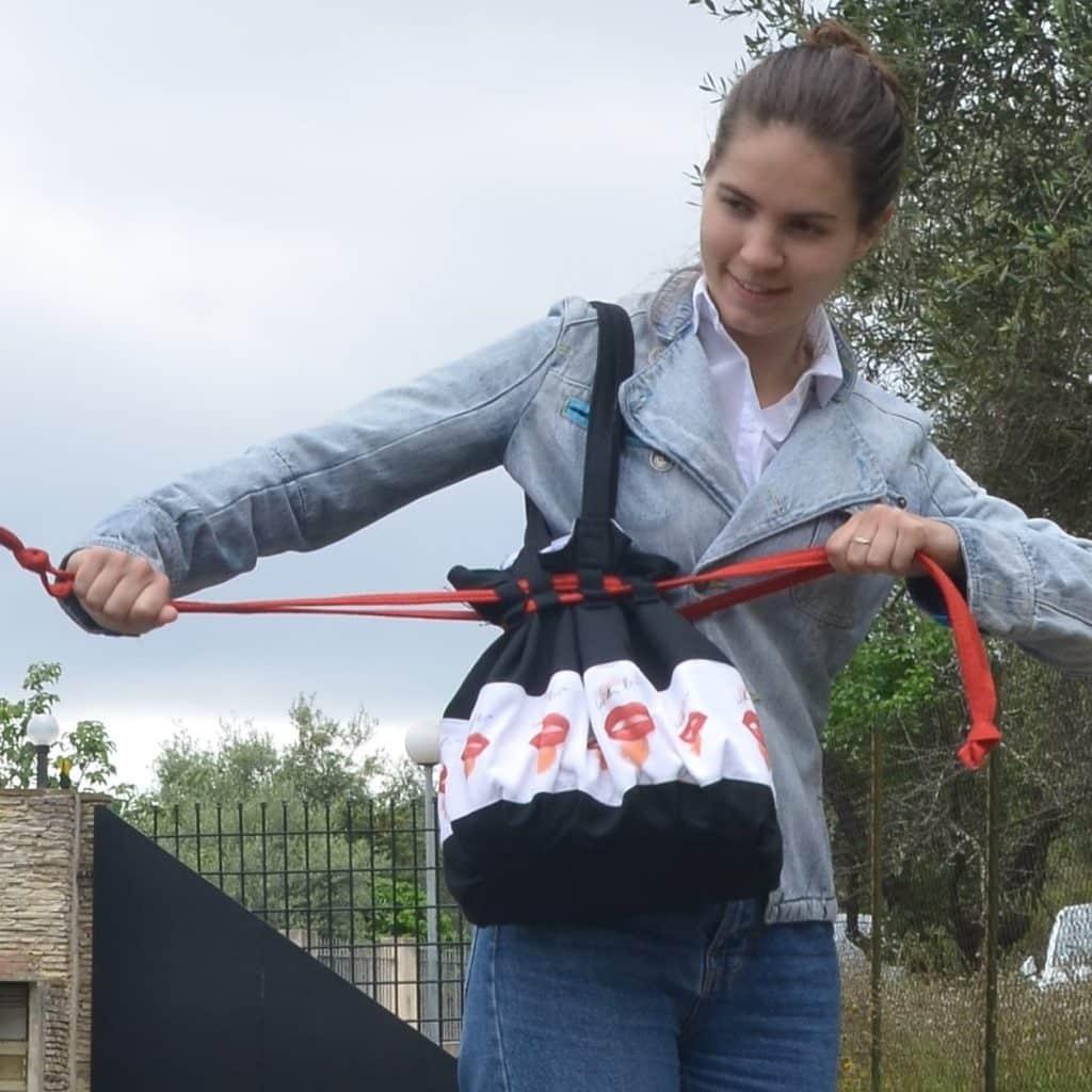 Femme qui ferme énergiquement son sac noir et rouge, signification du rouge