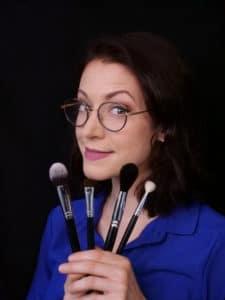 Femme avec des gra,des lunettes rondes, des cheveux noirs, un beau sourir et 4 pinceaux dans les mains