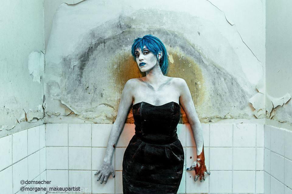 Bilal, Femme en robe de soirée noire décolletée aux épaules, debout dans une douche et une salle de bain délabrée, avec des cheveux bleus et une plaies sur la main droite, Body painting de l'artiste Morgane MakeUp artiste