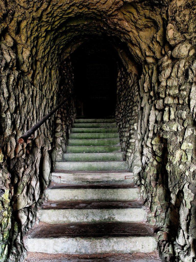Marches d'escalier qui montent dans une grotte noire, pour illustre l'incconu dans comment sortir de sa zone de confort