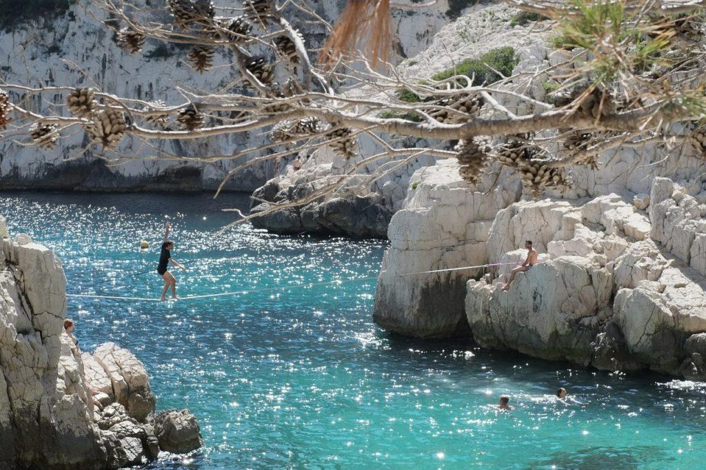 Slakeline tendu entre deux rochers au dessus de la mer, pour illsutre l'objectif de comment sortir de sa zone de confort.
