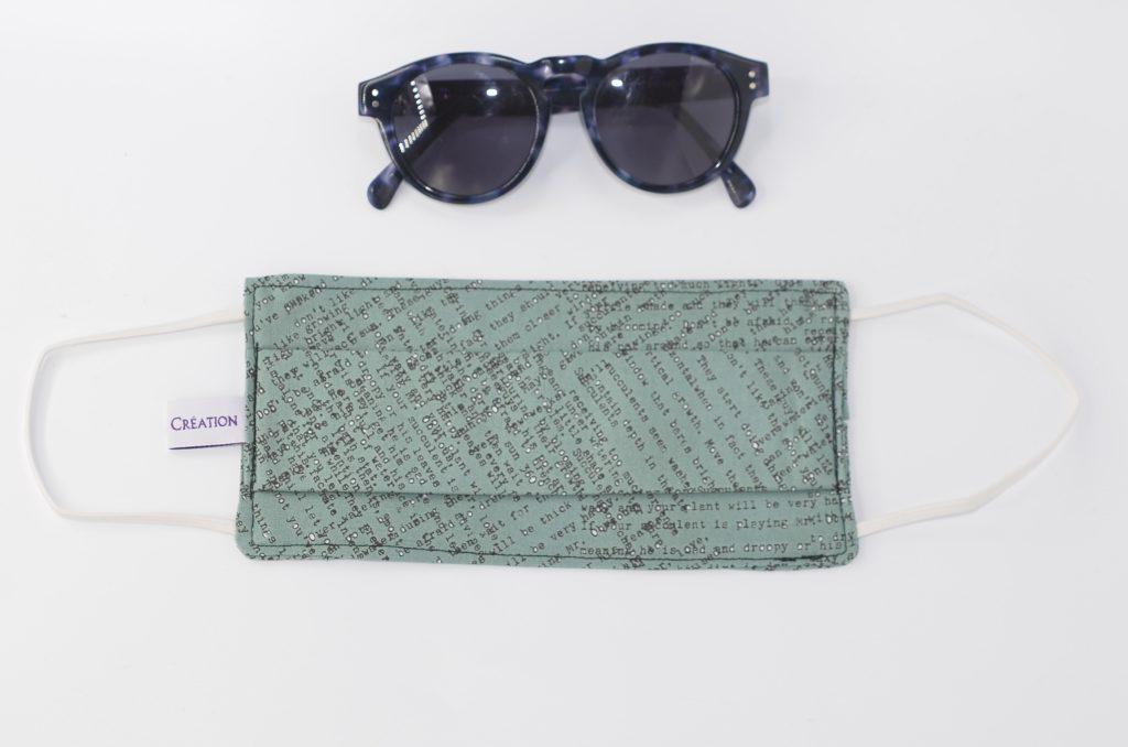 Masque en tissu vert avec des inscription noir; Lunettes de soleil posée sur un fond blanc