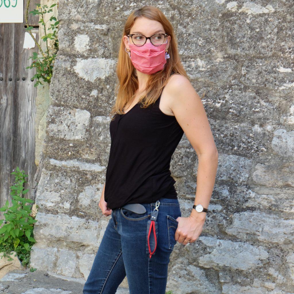 Jeune femme qui regarde au loin avec son masque personnalisé vichy rouge