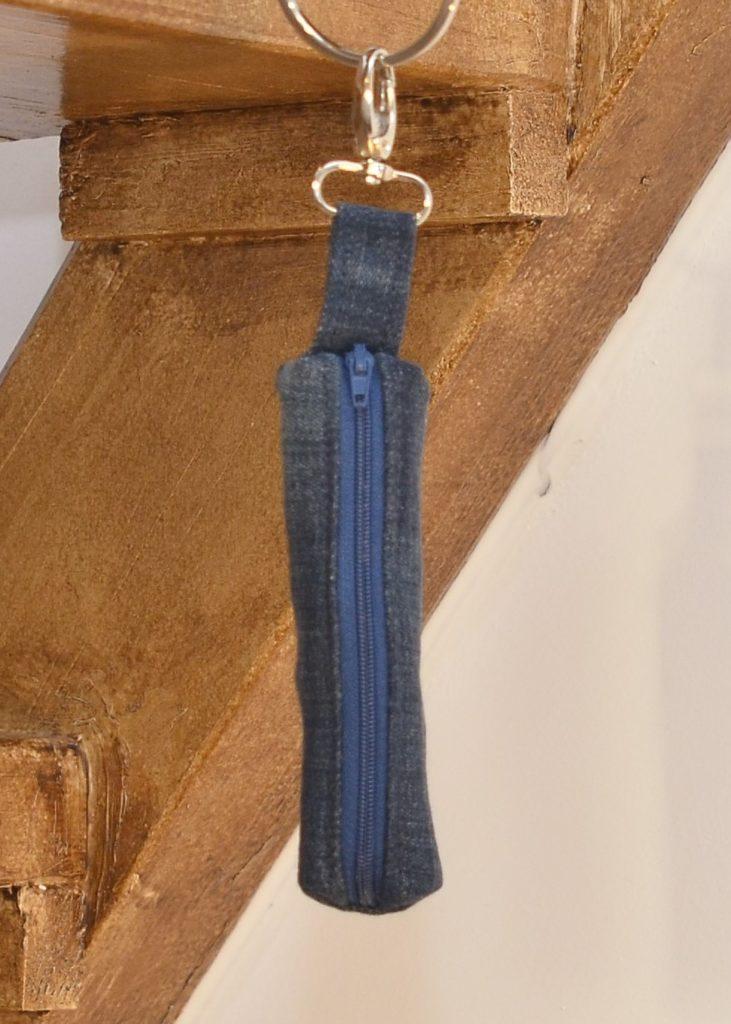 Pochette masque en jean recyclé bleu foncé et fermeture bleu marine, mousqueton argenté
