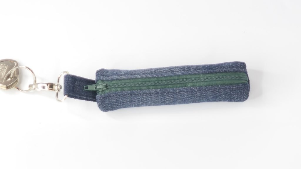Pochette masque en jean recyclé bleu foncé et fermeture verte, porte clé