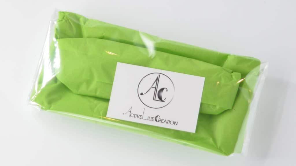 Pochette masque et masque emballé dans du papier de soie vert