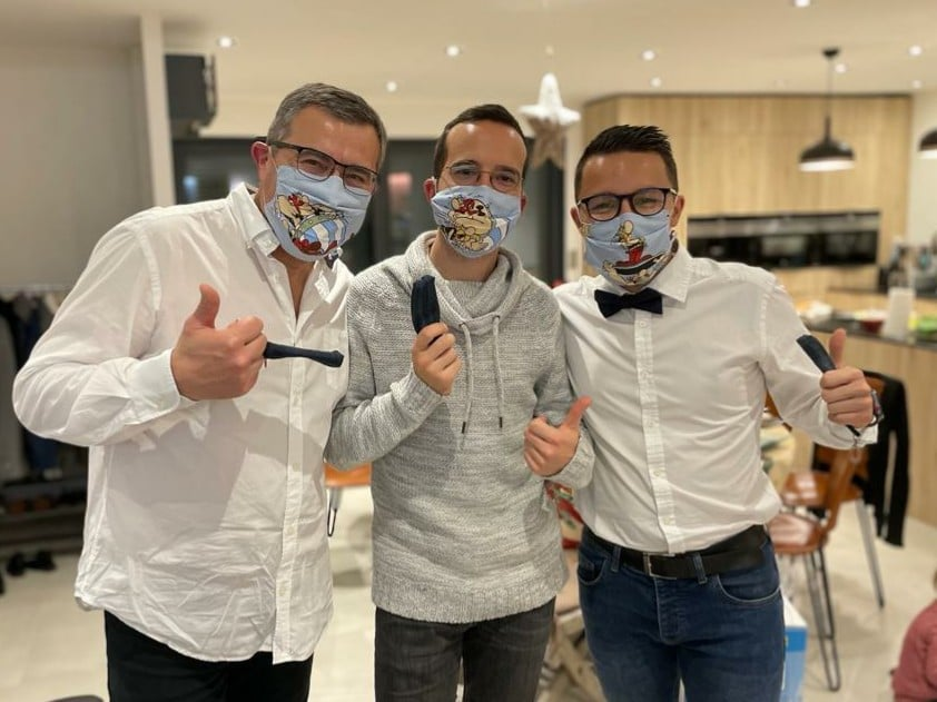 Trois hommes en chemises blanches et jean, avec chacun leur masque en tissu Asterix et leur pochette masque dans la main