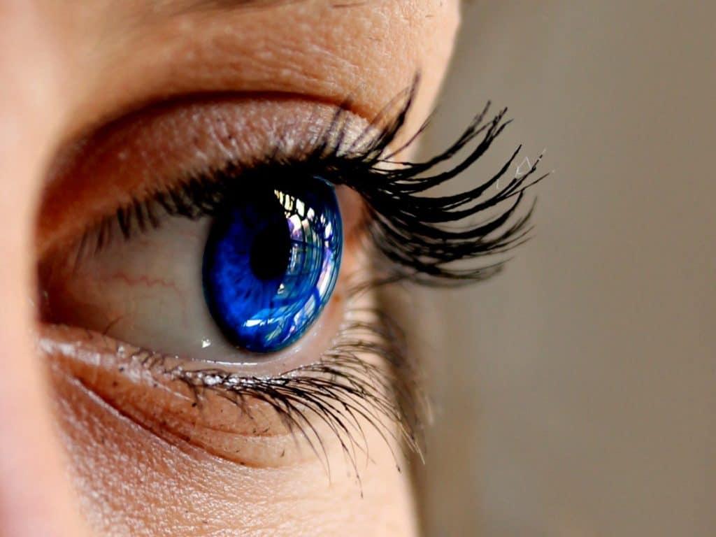 Gros plan sur un Oeuil ouvert d'un bleu profond. le bleu, élégance et créativité